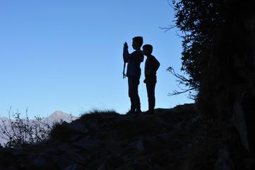 Zwei junge Wanderer fotografieren die Landschaft mit dem Smartphone (Silhouetteneffekt)
