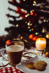 Cup of coffee, candle and cookies on table with winter and christmas decorations.