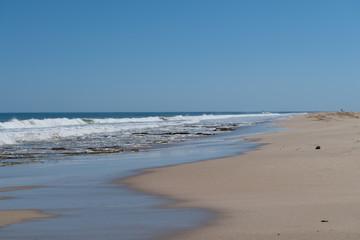 flaches Wellenspiel am langen Sandstrand