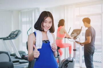 young happy asian woman slim body with towel showing thumbs up in fitness gym with people on machine bicycle background, bodybuilder, healthy lifestyle, exercise, workout and sport training concept