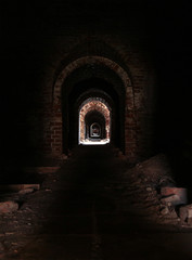 uninhabited horror horrible long corridor dark with a distant bright light, eerie catacombs with ruinous walls