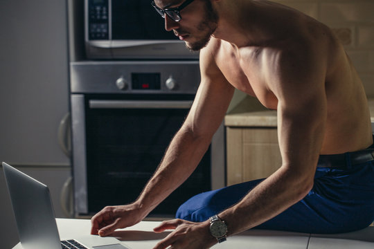 Physically Fit Man Using Laptop at home - Muscular Athletic Bodybuilder Fitness Model Use Computer