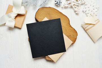 Mockup Christmas black greeting card letter in envelope and gift with white tree, flatlay on a white wooden background, with place for your text