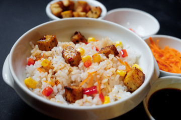 vegetarian rice salad with tofu and brown rice on black background.