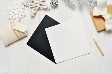 Mockup Christmas black greeting card letter in envelope and gift, flatlay on a white wooden background, with place for your text. Flat lay, top view photo mock up