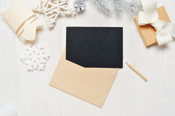 Mockup Christmas black greeting card letter in envelope and pencil, flatlay on a white wooden background, with place for your text, Flat lay, top view photo mock up