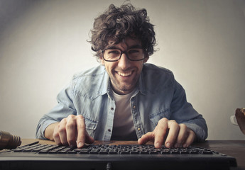 Smiling man using a pc