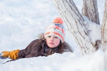Beautiful little girl playing in freshly fallen snow in winter park