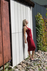 Young blond woman in a red dress leaning against the wooden wall..Businesswoman walking along the street and resting in the green city park on the beautiful sunny summer day.