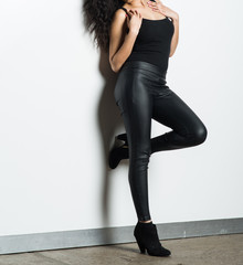 Model in a Black Tank Top and Tight Pants against a White Wall