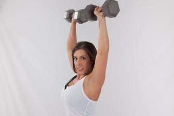 Lovely woman lifting dumb bells