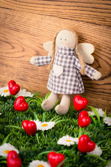 A textile doll with hearts on a green meadow
