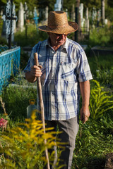 An elderly rural man in a straw hat is working near the grave in the cemetery.