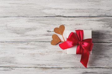 Gift or present box with red bow ribbon and  hearts on rustic background for Valentines day.