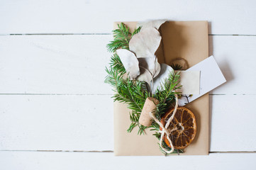 Craft envelopes with natural decoration on the white wooden desk.