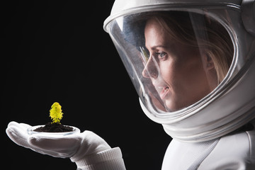 Feeling wonder. Close-up profile of amazed female astronaut is standing in helmet and holding on palm new form of green plant. She is expressing astonishment while looking at it. Isolated background