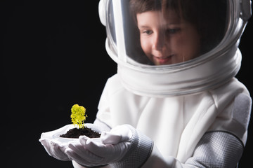 Discovering new forms. Close-up of hands with green plant of happy little astronaut wearing helmet and protective suit who is standing and feeling interest. Isolated background. Selective focus