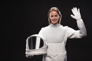 Hello. Portrait of friendly young attractive spacewoman is standing in full armor and holding helmet while waving her hand. She is looking at camera with smile. Isolated with copy space