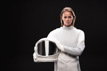 Portrait of confident young female cosmonaut wearing hyperbaric astronaut protective suit is standing and looking at camera seriously while holding helmet. Isolated background