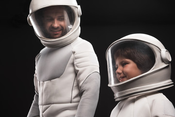 Always together. Optimistic father and his curious son wearing hyperbaric astronaut protective suit are standing and expressing gladness. Man is looking at child with smile. Isolated background