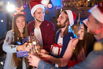 Group of friends having fun. young people laugh. celebrating New Year together. Group of beautiful young people in Santa hats. Blur Background.