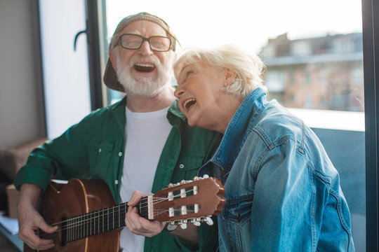 Carefree day. Portrait of mature male and female singing favorite song while playing on guitar at home