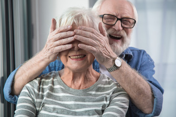 Surprise moment. Portrait of aged man and woman resting at home. Husband is closing eyes of wife with hands while she is smiling