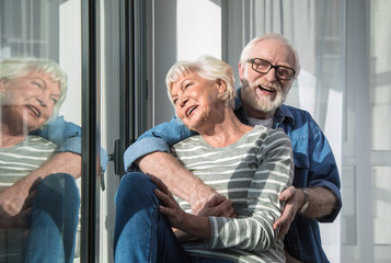 Light morning. Amused laughing senior man and woman cuddling each other while resting near window at living room