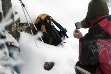 a hiker takes pictures with a smartphone an common vole that suddenly climbed onto his backpack
