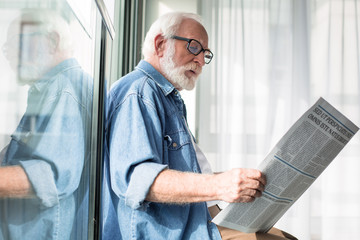 Smart occupation. Side view of interested pensioner reading favorite column in fresh newspaper