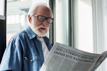 Portrait of old bearded pensioner enjoying newspaper at home. He is cheerful and interested