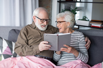 Sweet memories. Waist up portrait of smiling old sweethearts in glasses looking into notebook. They are laughing while wife is showing one funny sketch to beloved husband