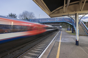 Fast express train passing through a Victorian UK station in southern England