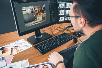 Side view bearded man having job with picture of cute dog in digital device while sitting at table in office. Profession concept