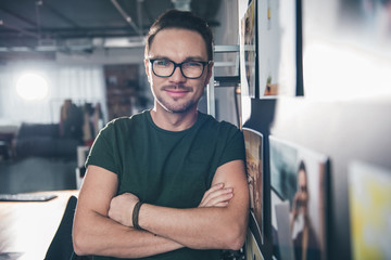 Portrait of smiling young man situating in office with pictures. Work and hobby concept