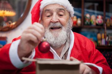 Santa Claus packing Christmas ball in box