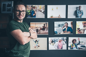 Portrait of beaming bearded man situating near wall with different photos in room. Creativity concept