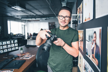 Portrait of beaming photographer keeping camera in arms while leaning against wall in office. Labor concept