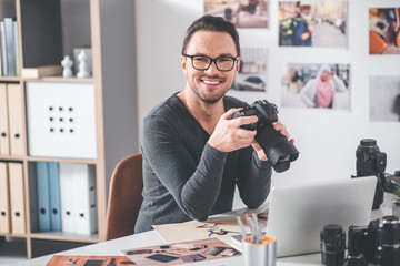 Portrait of smiling bearded man choosing pictures in camera while sitting at table in office. Work concept