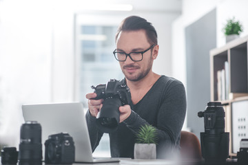 Portrait of smiling unshaven photographer watching at screen of gadget while sitting at table in office. Occupation concept