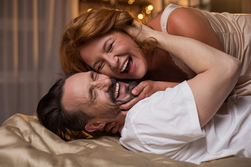 Obraz Portrait of excited married couple lying on bed and laughing. They are hugging with closed eyes - fototapety do salonu