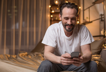 Portrait of happy male person messaging on cellphone at home. He is sitting on bed with relaxation and smiling. Copy space