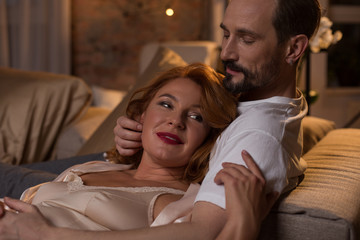 Happy with you. Portrait of relaxed woman enjoying affectionate hug of her husband. They are lying on bed and smiling