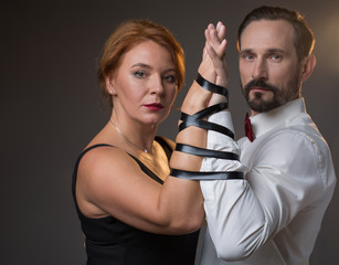 Forever together. Portrait of confident man and woman are holding hands tied by black tape. They are standing and looking at camera with seriousness. Isolated
