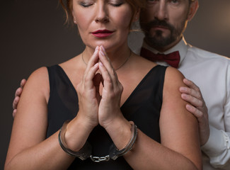 Fearful wife wants to get away from her husband. She is praying while being locked by manacles. Man is touching female shoulders with seriousness