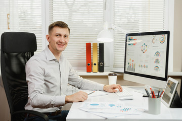Handsome smiling business man in shirt sitting at the desk, working at computer with modern monitor, lamp, folders, coffee or tea, documents in light office on window background. Manager or worker.