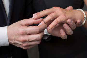 Close up of male hand wearing engagement ring on female finger. Proposal concept