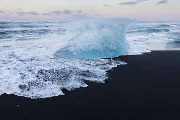 Iceland breaking Ice on black lava sand beach, winter natural sand beach background