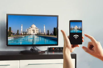 male hand holding a smartphone against view of living room