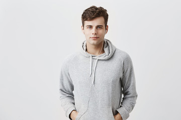 Handsome attractive European man in gray hoodie, with hands in pockets, look pleased at camera, has good mood as comes home after work. Good-looking male student poses against gray studio wall.